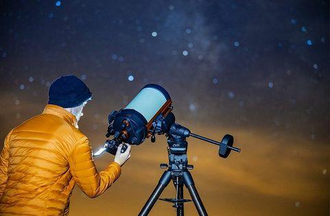 Canon EOS Ra s subjektom koji gleda u zaslon s promjenjivim kutom i narančastom jaknom